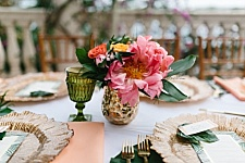 Pink peony centerpiece with peach napkins, gold chargers and tropical style.