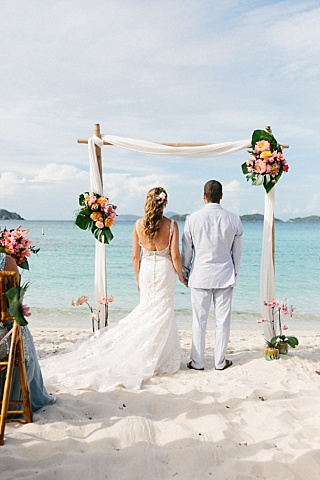 Bride and groom stand under bamboo wedding arch at beach wedding at Lindquist Beach in St. Thomas, Virgin Islands.