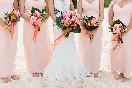Peach and pink tropical bouquets with pale pink and light peach bridesmaids chiffon dresses.