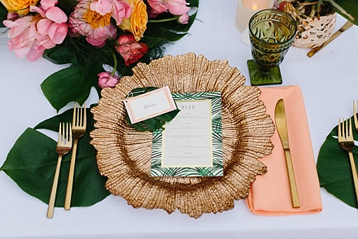 Gold charger plates with tropical leaves and greenery for wedding reception