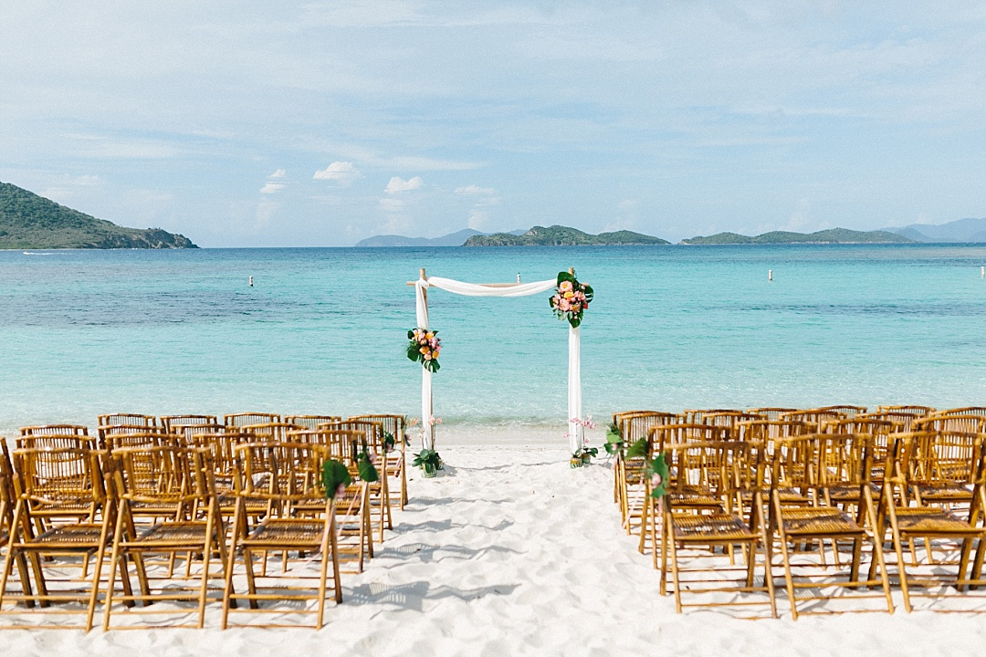 Lindquist beach wedding bamboo arch with tropical floral arrangements and brown bamboo folding chairs.