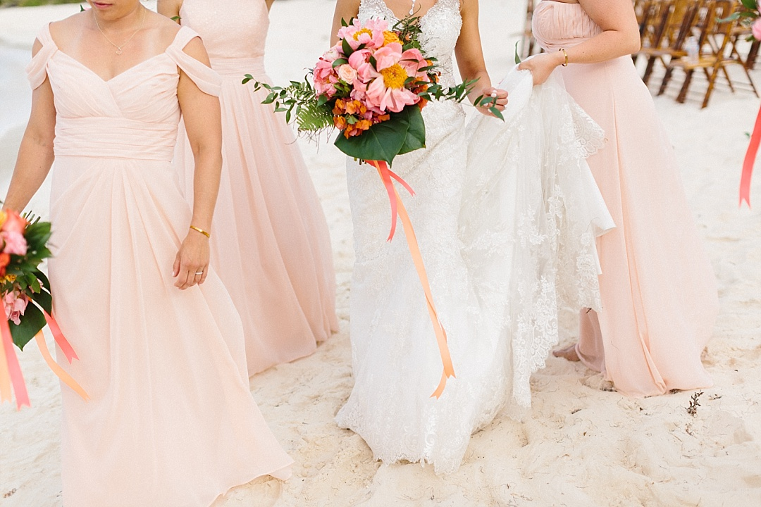 Bride and bridesmaids in pale, light peach long wedding gowns prepare to walk down the aisle.
