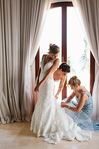 Bride gets dressed with her mother and bridesmaids.